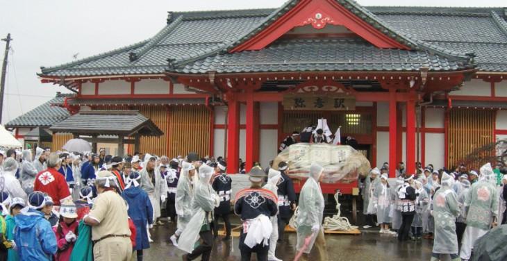 まず「初穂曳き」の参加者は弥彦駅前に集合します。この駅舎も彌彦神社をモチーフに造られています。駅の前に山車に積まれた初穂が用意されます。