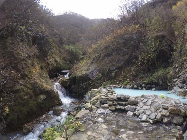 そしてこれが「河原の湯」です。白濁している湯は硫黄臭もちょっと強め。すぐ左には小川が迫り、露天風呂の背後は急な山肌です。