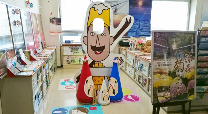 そしてこれが「レルヒさん」顔ハメです。顔ハメ・・・額の部分から顔を出す感じですね。阿賀野市などで作られている新潟県の郷土玩具「三角だるま」の特大があるのもポイントです。