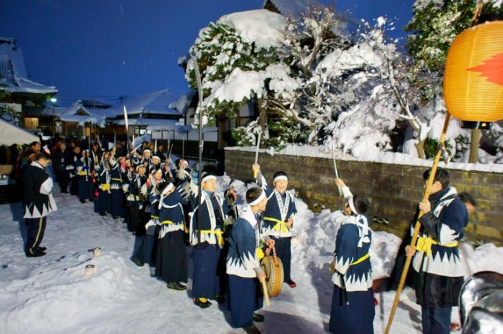午後5時。辺りも薄暗く、雪のちらつく中で、長徳寺の山門前に剣士たちが集合。「エイエイオー!」のかけ声とともに、パレードがスタートします。